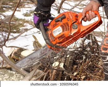 Bahno/Czech Republic - February 27, 2018: Man saws tree with an orange chain saw Husqvarna for gasoline to clean the old overgrown fence. He lopping it from the perimeter fence to make new wire mesh.