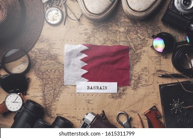 Bahrain Flag Between Traveler's Accessories on Old Vintage Map. Overhead Shot