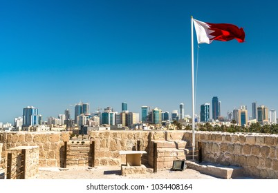 Bahrain Flag with skyline of Manama at Bahrain Fort. A UNESCO World Heritage Site in the Middle East
