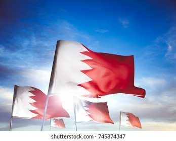 Bahrain flags waving with pride on a cloudy background / high contrast image