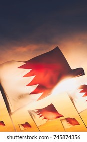 Bahrain flags waving with pride at sunset / high contrast image