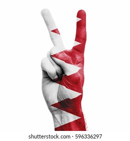 Bahrain national flag painted onto a male hand showing a V peace sign