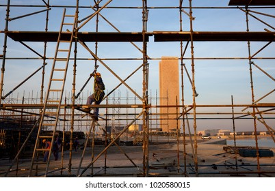BAHRIAN BAY, BAHRAIN - FEBRUARY 05: The technician working on the top of scaffold jacks platform for construction of Grandstand near water front at Bahrain Bay on February 05, 2018.
