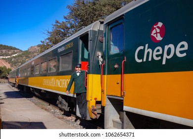 BAHUICHIVO, MEXICO - Jan 2016: A conductor leans out of the Chuhuahua-Pacifico (El Chepe) train at Bahuichivo railway station, in the Copper Canyon in northern Mexico