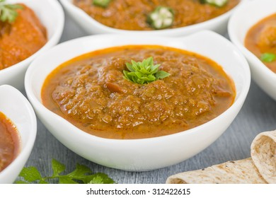 Baigan Bharta - Roasted mashed aubergines cooked with onions, tomatoes and spices. Chapattis and other vegetarian curries on background.