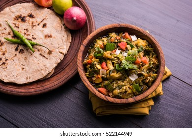 Baigan/Baingan Bharta - Mashed roasted Eggplant cooked with spices & vegetables. Served with Jowar flour flat bread known as bhakar/bhakri. served over colourful or wooden background. Selective focus
