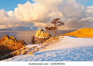 Baikal Lake in December. Magnificent sunset landscape of Olkhon Island in cloudy and snowy weather. View of the natural landmark - Shamanka Rock and the Wish Tree