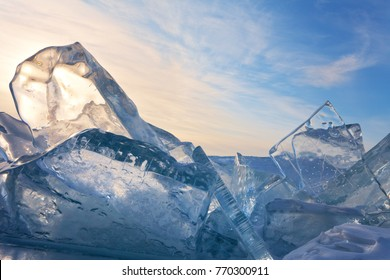 Baikal Lake in February sunset. Large blocks of transparent ice on ice hummocks against the blue sky