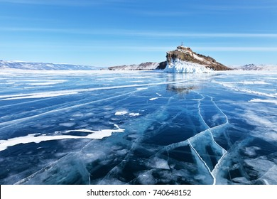Baikal Lake in February. View from the smooth blue ice to the lighthouse on the cliff Horin-Irgi of Olkhon Island