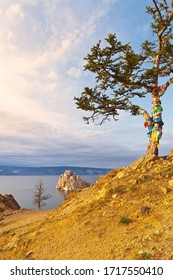 Baikal Lake. Island Olkhon. The famous Wish Tree with colored ribbons of tourists on a hill near the village of Khuzhir. View of the natural landmark Shamanka rock in sunset light. Beautiful landscape