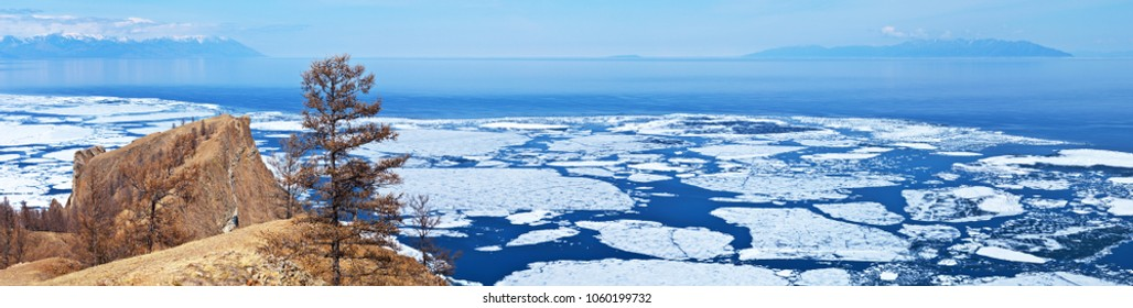 Baikal Lake in the May ice drift. Panoramic view of the famous cape Khoboy - the northern extremity of the island of Olkhon and the movement of white ice on the blue water