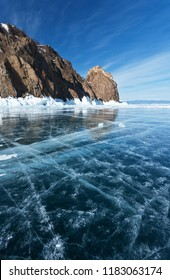 Baikal Lake. Olkhon Island. View from the blue ice to the famous Cape Khoboy or Virgin Rock (Skala Deva) at on sunny winter day