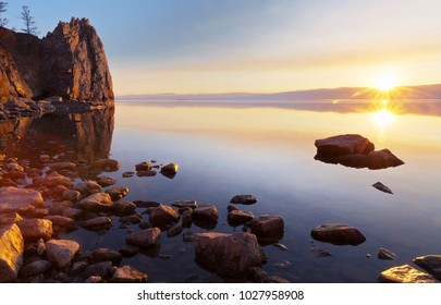 Baikal Lake on a May evening. Spring sunset at the Olkhon Island. The coastal rocks are reflected in clear water