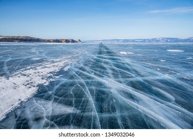 Baikal lake, Road trip, Travel concept, Road way on surface of the natural ice in frozen water behind the mountain island at Baikal lake, Russia, 2019
