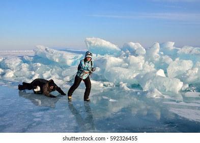 Baikal lake, Russia, March, 01, 2017. Tourists pull each other on a sled in front of the ice ridges near the village of Bolshie Koty at lake Baikal