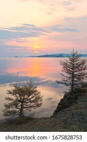 Baikal Lake in the spring at dawn. The rising sun over the Strait of Small Sea. Beautiful quiet landscape with larch trees on the shore in the early morning. Natural background