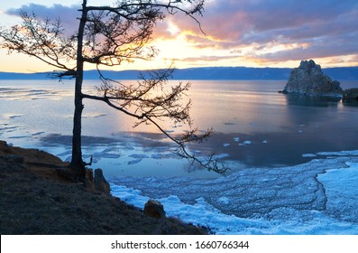 Baikal Lake in the spring. Magnificent sunset landscape of Olkhon Islands. View of the natural landmark - Shamanka rock in May evening. Natural background