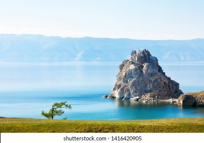 Baikal Lake in summer. View of the natural landmark of Olkhon Island - Shamanka Rock at June afternoon. Lake natural background. Beautiful landscape. Place for text