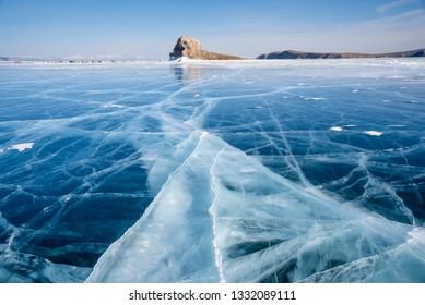 Baikal lake in winter day. Cracks on surface of the natural ice in frozen water behind the cliffs of Olkhon Island at Baikal lake, Russia