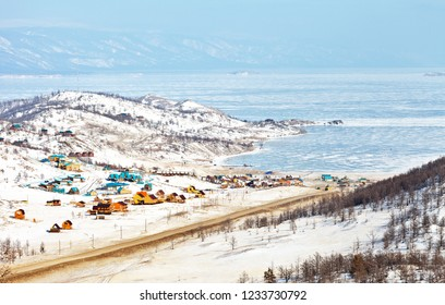 Baikal Lake in winter. The road to the ice crossing the Small Sea Strait to the Olkhon Island. Tourist wooden houses on the shore of the Kurkut Bay