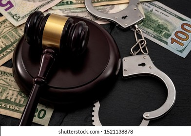 Bail bond system, bailing out of jail and innocent until proven guilty conceptual idea with judge wooden gavel, dollar banknotes and handcuffs