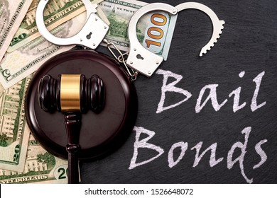 Bail bond system, bailing out of jail and innocent until proven guilty conceptual idea with judge wooden gavel, dollar banknotes and handcuffs with text Bail Bonds