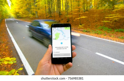 Baila Tusnad, Romania, - October 15, 2017 : hand holding Smarthphone and using Uber app on road with car. Trying to get car request in rural area.
