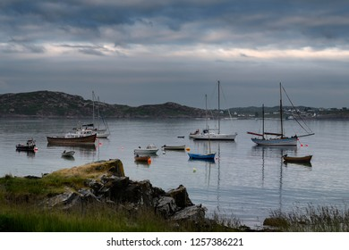 Baile Mor, Isle of Iona, Scotland, UK - June 10, 2018: Baile Mor village harbour at dusk with moored boats and sailboats on the Sound of Iona looking from Isle of Iona to Fionnphort Isle of Mull