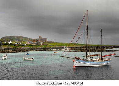 Baile Mor, Isle of Iona, Scotland, UK - June 10, 2018: Iona Abbey at Baile Mor village on Isle of Iona in morning cloud with sailboat on Sound of Iona Inner Hebrides Scotland UK