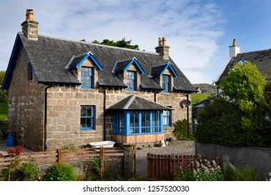 Baile Mor, Isle of Iona, Scotland, UK - June 10, 2018: Stone house with blue trim and flower garden on main street of Baile Mor village on Isle of Iona Inner Hebrides Scotland UK