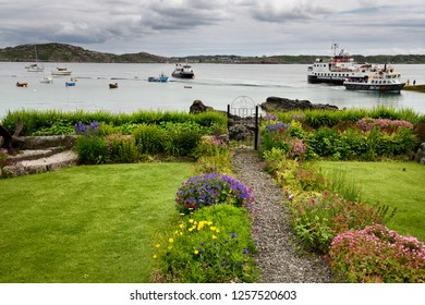 Baile Mor, Isle of Iona, Scotland, UK - June 10, 2018: Baile Mor garden on Isle of Iona looking out to Sound of Iona and Fionnphort with docked Ferry and tour boats and sailboats Scotland