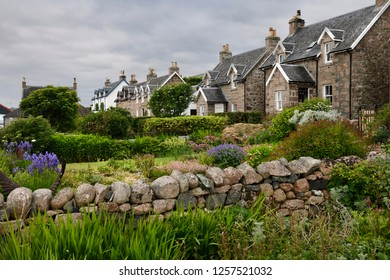 Baile Mor, Isle of Iona, Scotland, UK - June 10, 2018: Flower gardens under cloudy sky with stone houses of Baile Mor village on Isle of Iona Scotland UK