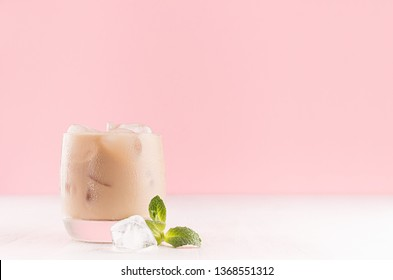 Baileys liqueur in misted glass with ice cubes and green mint on pastel pink background and white wooden table, copy space.