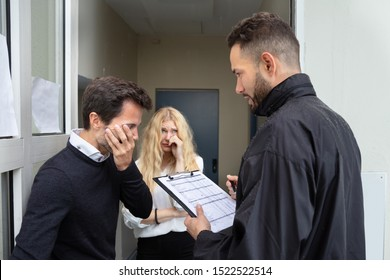 Bailiff Talking With Sad Couple At Home Entrance