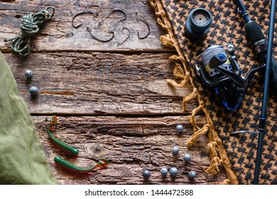 baits, hooks, fishing rod on the wooden background with space for text