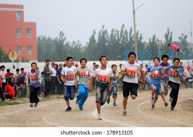 BAIXIANG COUNTY, HEBEI PROVINCE, CHINA - MAY 10, 2013: Baixiang County Middle School Track Meet held. Unidentified student athletes struggling to compete in a race against the project.