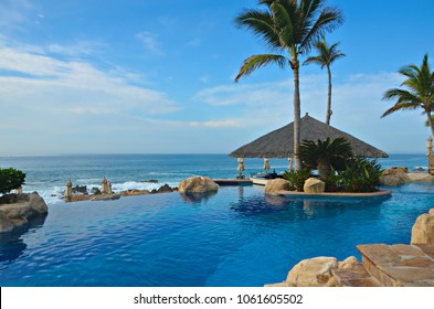 Baja California, Mexico. July 31, 2017. Panoramic resort pool view of a Straw Roof wooden Hut, in a relaxing setting, surrounded by palm trees overlooking the blue waters of the Pacific Ocean.