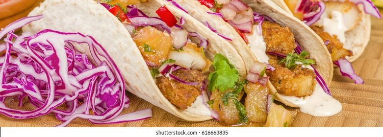 Baja Fish Tacos - Soft shell tacos filled with seasoned fried white fish served with red cabbage, pineapple salsa, chunky guacamole and creamy Baja style sauce.