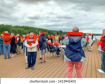 Baja, Hungary - May 23, 2019 :  Senior tourists on river cruise participating in safety drill on deck of ship.