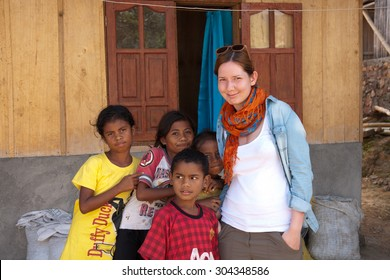 BAJAWA, FLORES - INDONESIA - CIRCA JULY 2013: Humanitarian worker posing with children in Indonesian village that belongs to Naga tribe