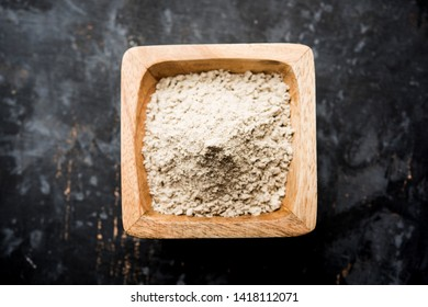 bajra  atta / flour of pearl millet served in a bowl with small wooden scoop, selective focus