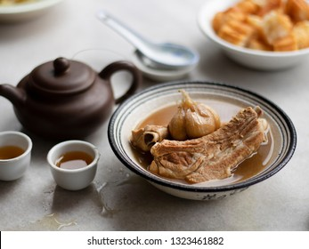 Bak kut teh or Bakut is a pork rib dish cooked in broth, served in Malaysia and Singapore. Bak kut teh and tea pot. Bak kut teh with dough fritters.