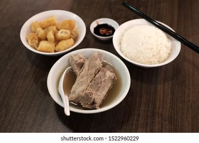Bak Kut Teh served with rice and char kway (strips of fried dough) in a white bowl.