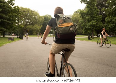Bakc view of modern hipster man riding bike in the park, photographed in Brooklyn, NY