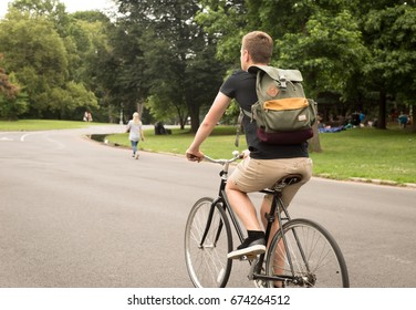 Bakc view of modern hipster man riding bike in the park, photographed in Brooklyn, NY in July 2017