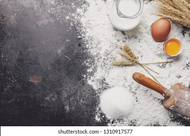 Bake dough recipe ingredients eggs, flour, milk, butter, sugar and rolling pin on dark background. Background with free text space