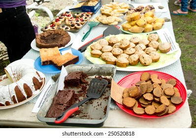 A bake sale is in full progress. All items for sale have been labeled with ingredients for the benefit of those with food allergies.