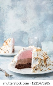 Baked Alaska, chocolate and strawberry ice cream cake with meringues, selective focus