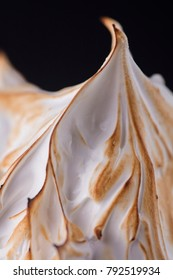 baked alaska desert on black background
