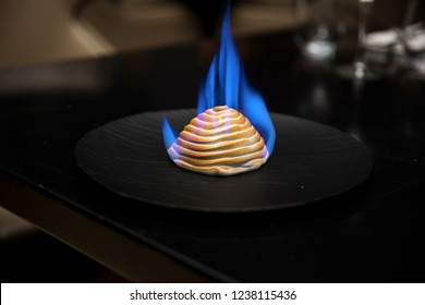 Baked Alaska on a black plate with flames